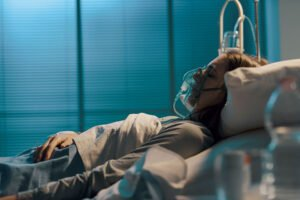 Woman with oxygen mask lying in a hospital bed at night, medicine and healthcare concept