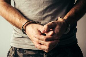 Handcuffed soldier in military army clothes. Prisoner of war or arrested terrorist, close up of hands in handcuffs
