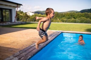 Two small children playing and jumping in swimming pool outdoors.