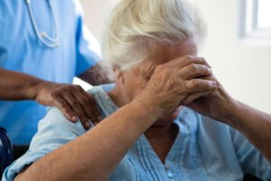 Midsection of nurse consoling senior woman at nursing home