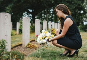 young widow laying flowers at her husband's grave
