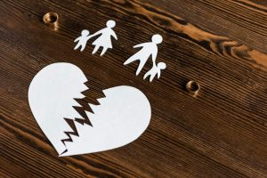 broken paper heart and paper family on wooden table blog post what evidence do you need to prove adultery